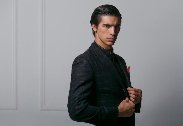 Ritratto orizzontale di bel giovane in abito nero con sciarpa di seta rossa in tasca, pose di profilo, su sfondo bianco.