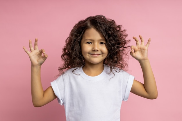 Ritratto orizzontale di gioiosa bambina con i capelli ricci, guardando sorridente, mostrando segno giusto con entrambe le mani