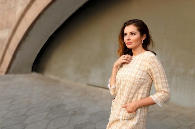 Ritratto orizzontale di una donna dai capelli rossi in un elegante abito classico pensando, aspettando fuori.