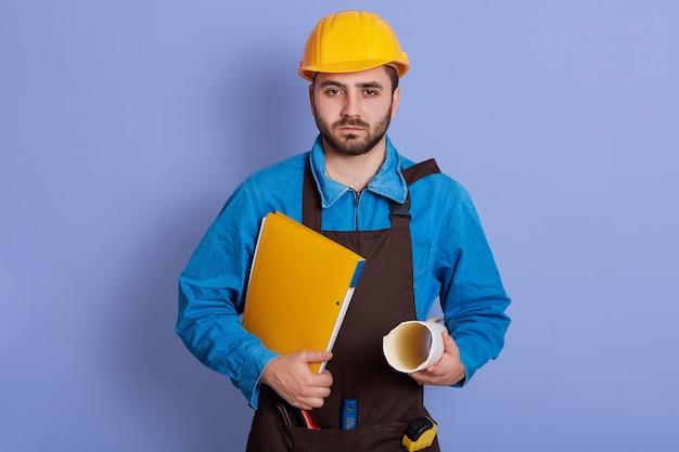 Ritratto orizzontale del giovane bello serio che tiene progetti e documenti in entrambe le mani, indossando l'uniforme, insoddisfatto del lavoro. concetto di processo di lavoro.