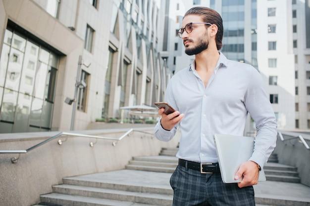 Ritratto orizzontale di giovane uomo attraente in piedi sui gradini e guarda a sinistra. sembra moderno ed elegante. guy tiene in mano laptop e telefono. il giovane sembra serio.
