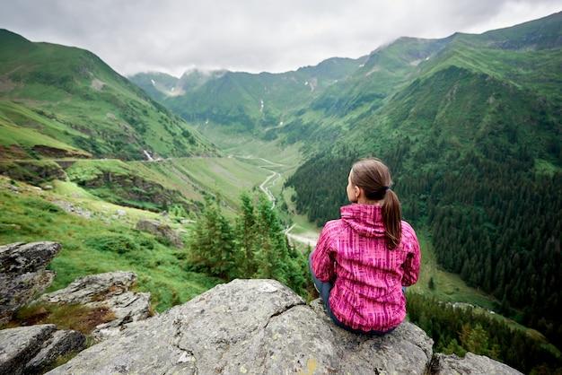 Colpo orizzontale di retrovisione di un viaggiatore femminile che gode del paesaggio sbalorditivo delle montagne che si siede sul bordo di una roccia