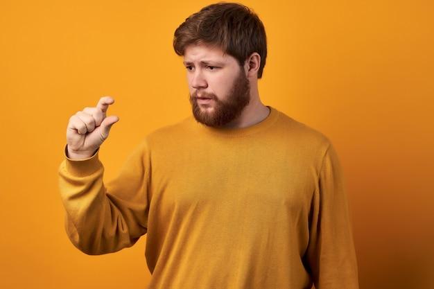 Il colpo orizzontale del maschio barbuto stupito mostra qualcosa di molto piccolo, indossa una camicia di jeans casual, isolato su sfondo bianco