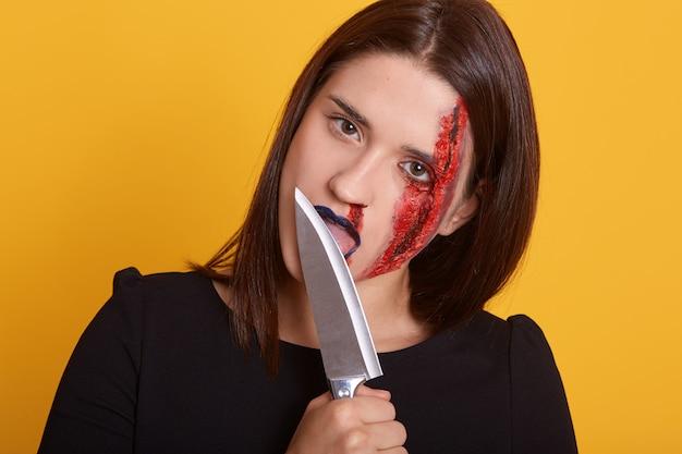 Colpo orizzontale della ragazza attraente tutto nel sangue con la lama del coltello sentire la sua lingua