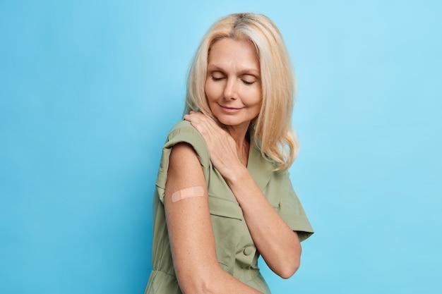 Il colpo orizzontale della donna europea bionda indossa l'intonaco sul braccio ha ottenuto la vaccinazione per proteggersi dal coronavirus ha bisogno del certificato di immunizzazione covid 19 posa contro il muro blu dello studio