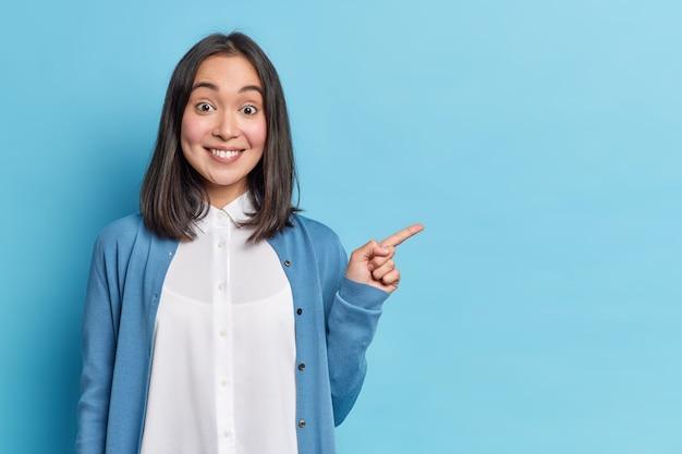 Il colpo orizzontale di una bella donna asiatica allegra indica che mostra a parte che un buon affare consiglia che il prodotto indossi una camicia bianca vicino