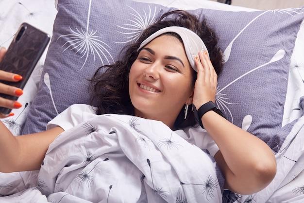 Il colpo orizzontale della donna sveglia a letto con il telefono cellulare che fa il selfie, esaminando lo schermo del dispositivo con l'affascinante sorriso felice, tiene la mano sulla fronte sulla maschera di sonno, stendendosi a letto sotto la coperta bianca.