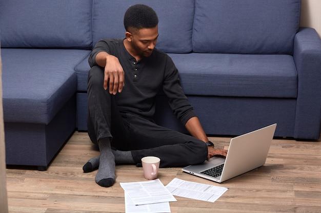 Colpo orizzontale di giovane maschio bello dalla pelle scura che fa lavoro di ufficio a casa, controllando i documenti