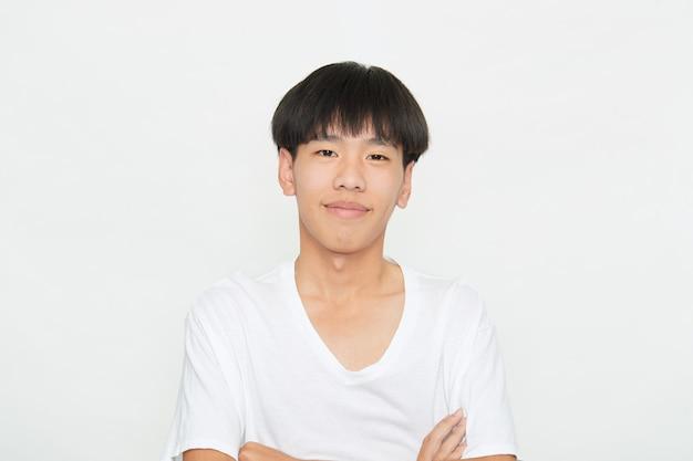 Inquadratura orizzontale di un bel ragazzo giovane con l'espressione positiva degli occhi marroni, essendo lodato da qualcuno, vestito casualmente, isolato muro bianco