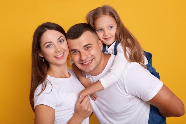 Colpo orizzontale della famiglia felice che indossa camicie bianche, stand sorridente isolato su studio giallo, padre che trasporta sulle spalle il suo adorabile bambino femmina. concetto di relazione, felicità e devozione.