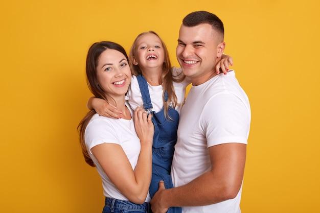 Colpo orizzontale della famiglia felice con un bambino, guardando sorridendo direttamente alla telecamera