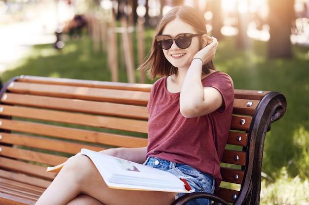 Colpo orizzontale di felice giovane studentessa indossare sfumature e maglietta, legge la rivista sul banco nel parco, ha un sorriso positivo, pone contro il verde offuscata. concetto di persone e ricreazione