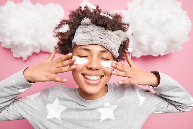 Inquadratura orizzontale di felice donna afroamericana applica toppe di bellezza sotto gli occhi per ridurre il gonfiore dopo aver dormito sorrisi ampiamente indossa indumenti da notte sleepmask ha piume nei capelli