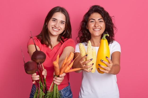Un colpo orizzontale di due donne caucasiche del brunette che tengono le verdure in mani