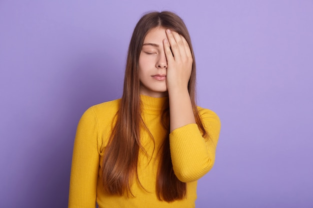 Colpo orizzontale della donna turbata che sta contro lo studio lilla