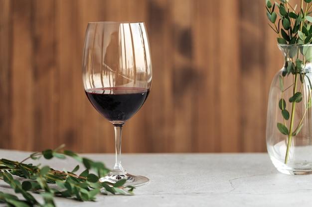 Vista laterale orizzontale su un bicchiere di vino rosso sul tavolo decorato con foglie
