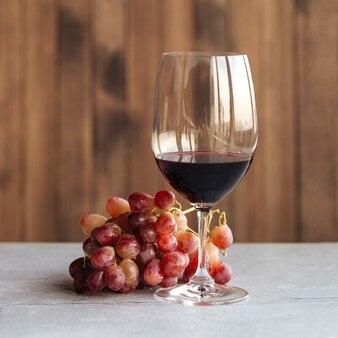 Vista laterale orizzontale su un bicchiere di vino rosso con uva sul tavolo
