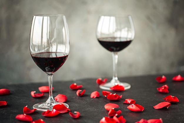 Vista laterale orizzontale su un bicchiere di vino rosso sul tavolo decorato con petali