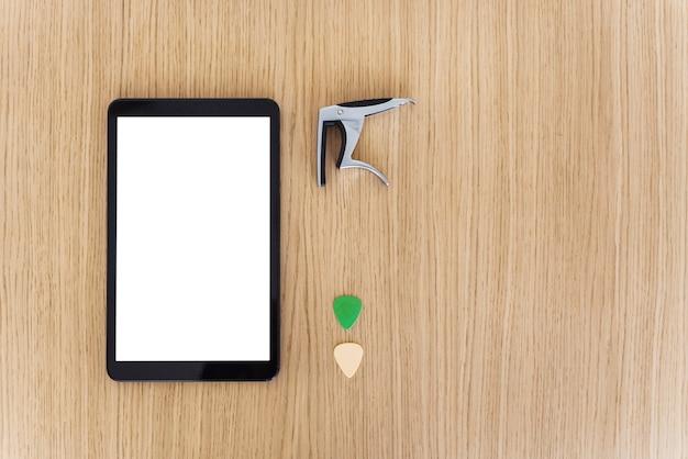 Vista superiore orizzontale dello schermo dello smartphone con contenuto vuoto. studia e impara il concetto online delle lezioni di chitarra. esplora musica e tecnologia. plettri per chitarra, armonica e ponte per chitarra.