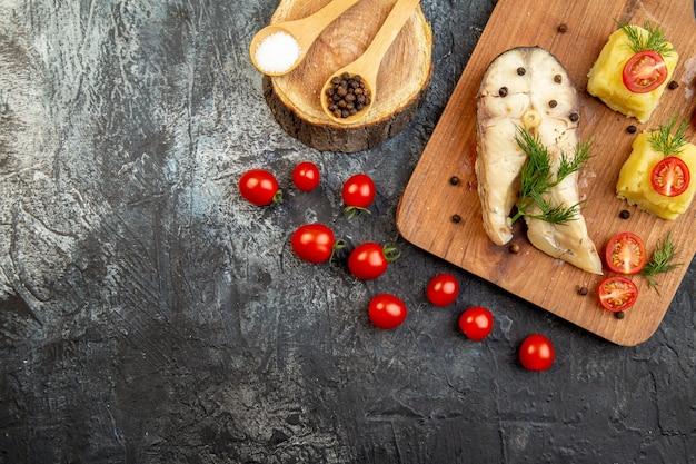 Vista orizzontale di farina di grano saraceno di pesce bollito servita con pomodori formaggio verde su tagliere di legno spezie sulla superficie del ghiaccio