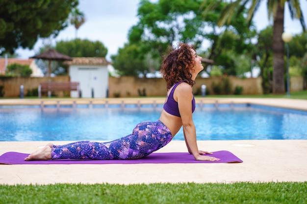 Vista orizzontale della donna caucasica che respira all'aperto e pratica yoga durante le vacanze estive accanto a una piscina. stile di vita fitness, esercizio fisico e abitudini sane all'aperto.