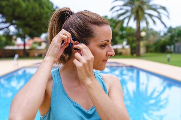 Vista orizzontale della donna caucasica utilizzando tappi per le orecchie sportivi accanto a una piscina. stile di vita fitness, esercizio fisico e sane abitudini all'aperto in estate.