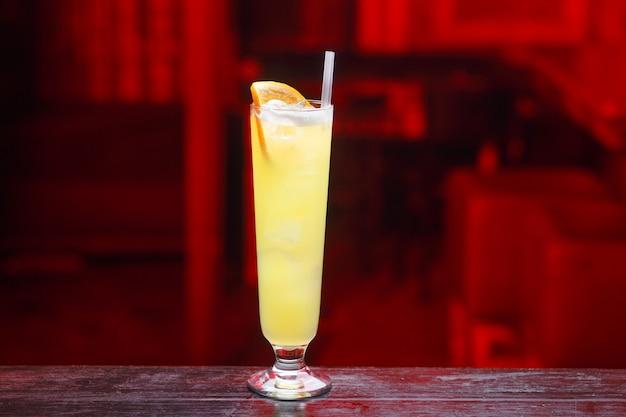 Vista orizzontale. primo piano di un lungo bicchiere di succo d'arancia con gin, che si trova sul bancone del bar, isolato su uno spazio a luce rossa.