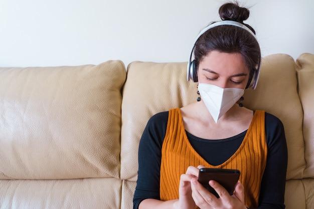 Vista orizzontale della maschera da portare d'uso della donna malata che chiama un amico a casa. stare a casa. malattia da virus pandemico covida 19. concetto di salute.