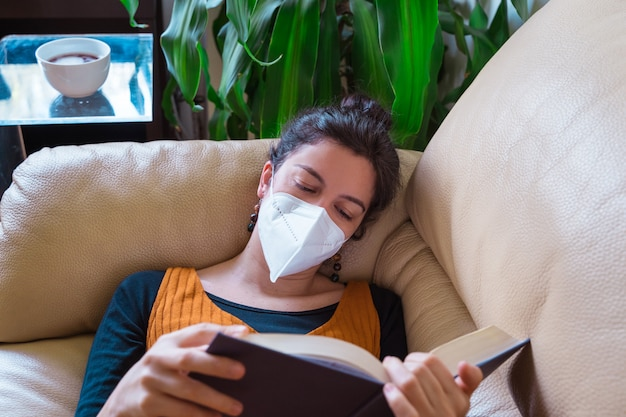 Vista orizzontale della maschera da portare d'uso della donna malata che legge un libro a casa. stare a casa. malattia da virus pandemico covida 19. concetto di salute.