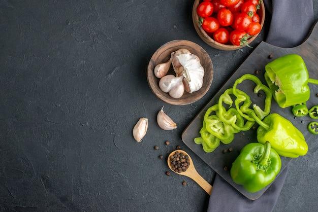 Vista orizzontale di peperoni verdi tritati tagliati interi su tagliere di legno pomodori in ciotola aglio su asciugamano di colore scuro sul lato sinistro sulla superficie nera