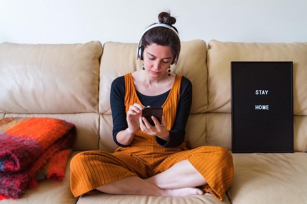 Vista orizzontale della donna che ascolta la musica a casa. stare a casa. malattia da virus pandemico covida 19. concetto di salute.