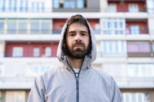 Vista orizzontale del giovane uomo isolato davanti a piccoli appartamenti economici all'aperto.