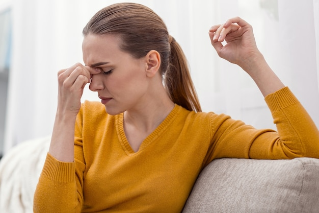Orribile mal di testa. bella donna esausta malata che massaggia il ponte del naso mentre gira la testa di profilo e posa sulla luce