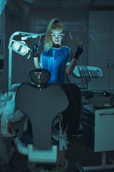Scena dell'orrore nell'ufficio del dentista. pazzo stomatologo malvagio ucciso paziente in poltrona odontoiatrica. maniaco pazzo, dottore assassino.