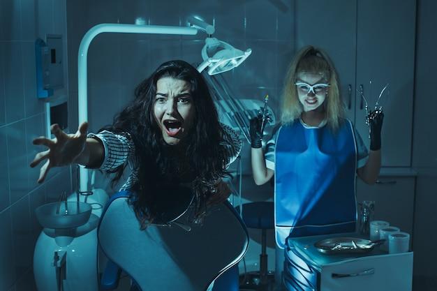 Scena dell'orrore nell'ufficio del dentista. stomatologo diabolico pazzo che cura i denti al paziente spaventato in sedia dentaria maniaco pazzo, dottore assassino.