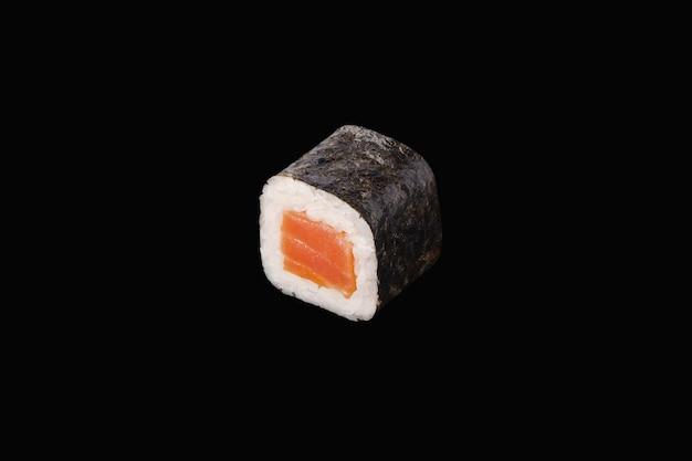 Rotolo di hosomaki con salmone affumicato isolato sul nero