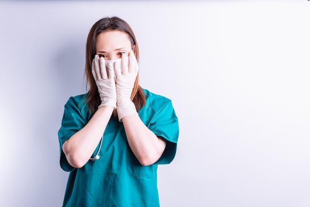 Medico ospedaliero con guanti per maschera facciale stetoscopio con le mani sul viso con simbolo di sopraffazione o stanchezza