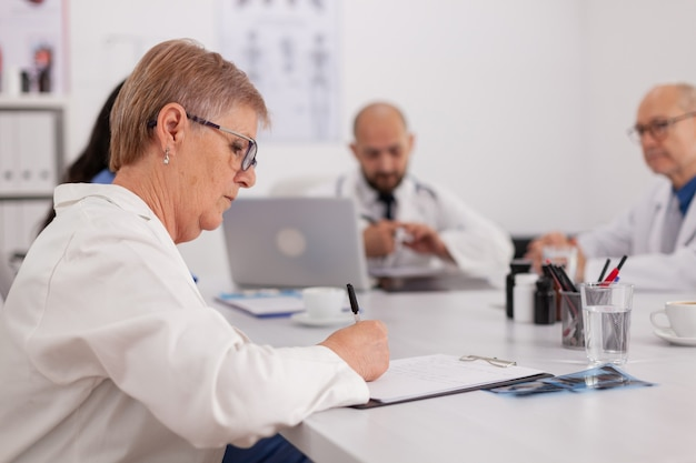 Medici ospedalieri che lavorano alla presentazione di competenze mediche che prescrivono farmaci in pillole seduti alla scrivania nella sala riunioni della conferenza. lavoro di squadra che pianifica il trattamento sanitario
