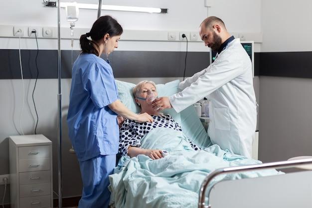 La donna anziana ricoverata inspira ed espira attraverso la maschera di ossigeno che giace nel letto d'ospedale. infermiera medica utilizzando lo stetoscopio che ascolta il cuore del paziente
