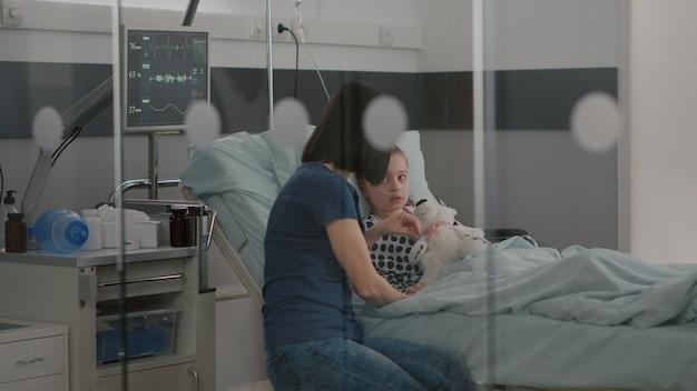 Bambino malato ricoverato che riposa a letto indossando un tubo nasale che si riprende dopo un intervento medico