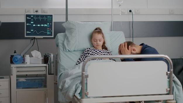 Figlia malata ricoverata che dorme dopo aver subito un intervento medico