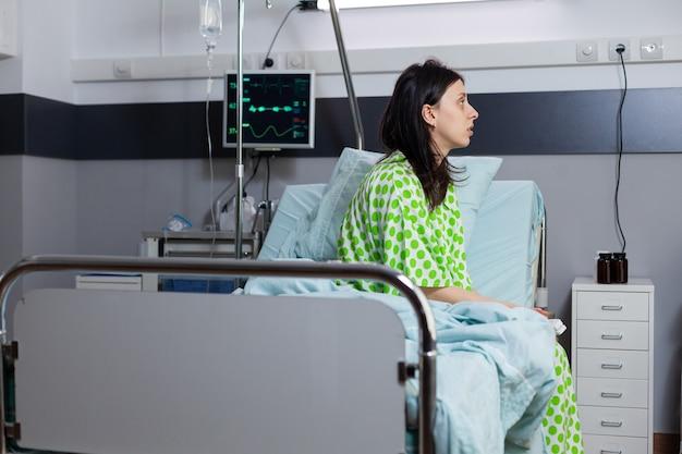 Donna malata ospedalizzata con malattia in via di guarigione dopo un intervento medico seduto sul letto nel reparto ospedaliero durante il recupero in attesa di consultazione