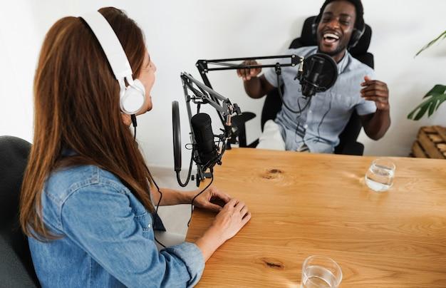 Host che hanno una sessione di podcast insieme - relatore femminile che fa un'intervista durante lo streaming live - concetto di tendenze tecnologiche - focus sul microfono sinistro