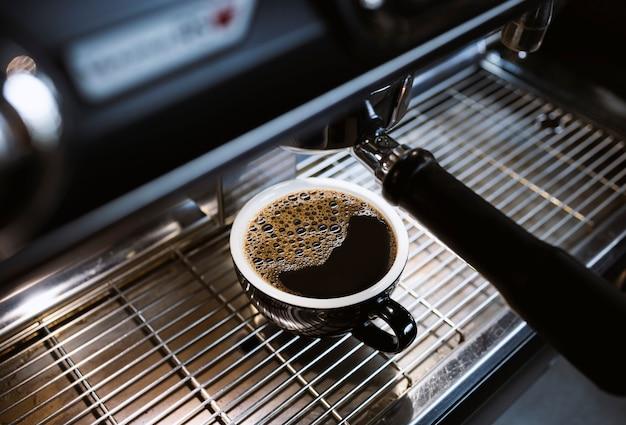 Americano caldo sulla macchina del caffè nella caffetteria con soft-focus e luce in sottofondo