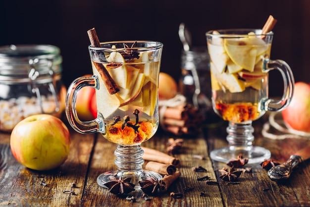 Sidro di mele caldo e ingredienti sulla tavola di legno