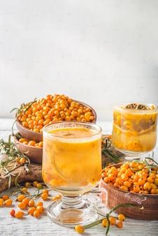 Bevanda biologica autunnale calda. bevanda dietetica sana, cibo buster immunità. tè all'olivello spinoso con arancia e miele in coppe di vetro. spazio bianco della copia del fondo