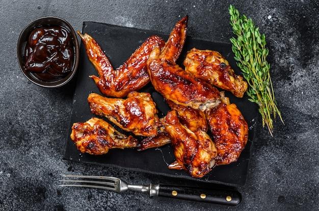 Hot barbecue ali di pollo con salsa barbecue. sfondo nero. vista dall'alto.