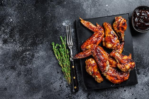 Hot barbecue ali di pollo con salsa barbecue. tavolo nero. vista dall'alto. copia spazio.