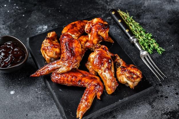Hot barbecue ali di pollo con salsa barbecue. tavolo nero. vista dall'alto.