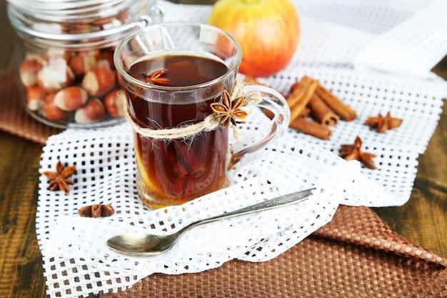 Bevanda calda in tazza di vetro con frutta e spezie, su fondo in legno